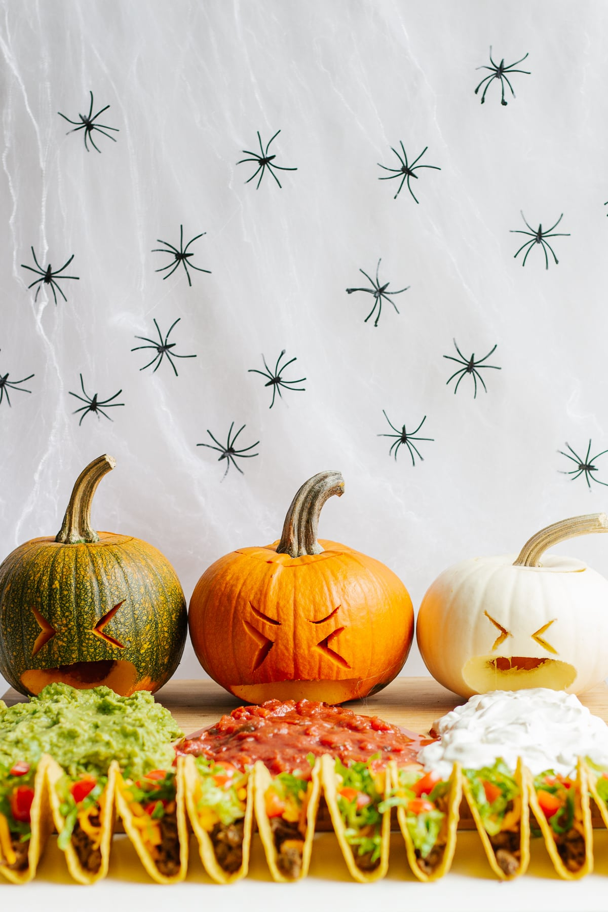 """A board with three carved pumpkins """"puking"""" out guacamole, salsa and sour cream with a row of tacos in front."""