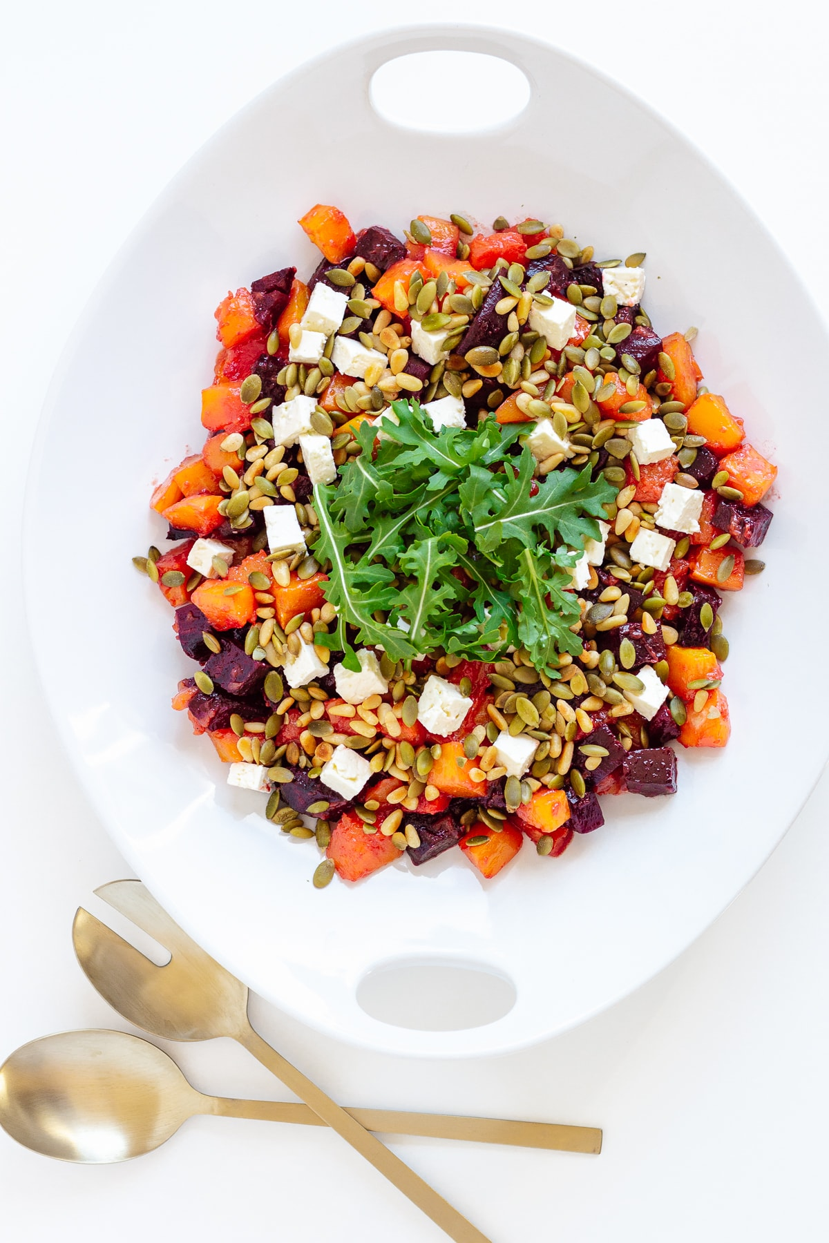 Pumpkin and beetroot salad in a white serving dish with matte gold coloured salad servers.