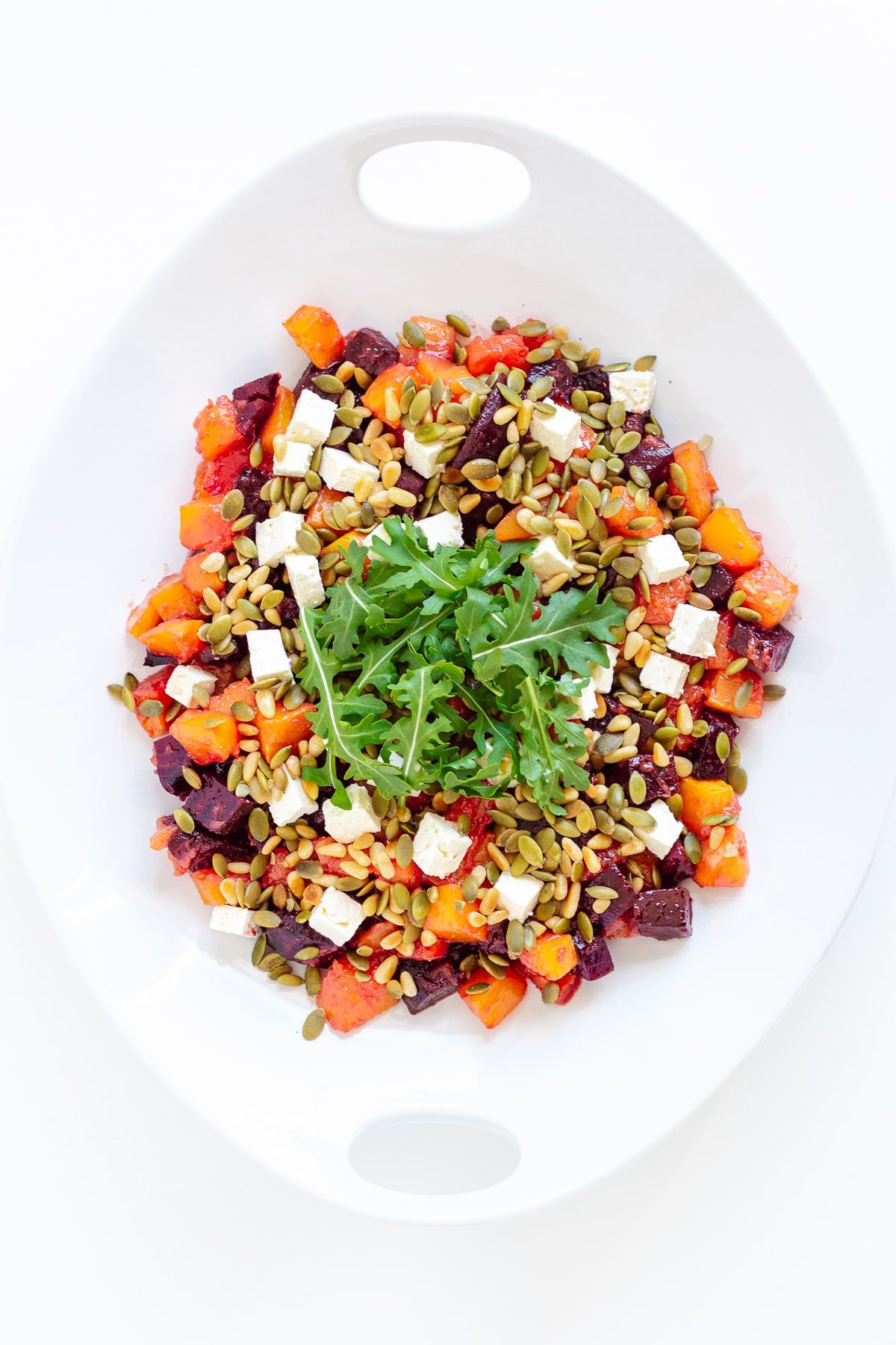 Roasted pumpkin and beetroot salad on a white serving platter.