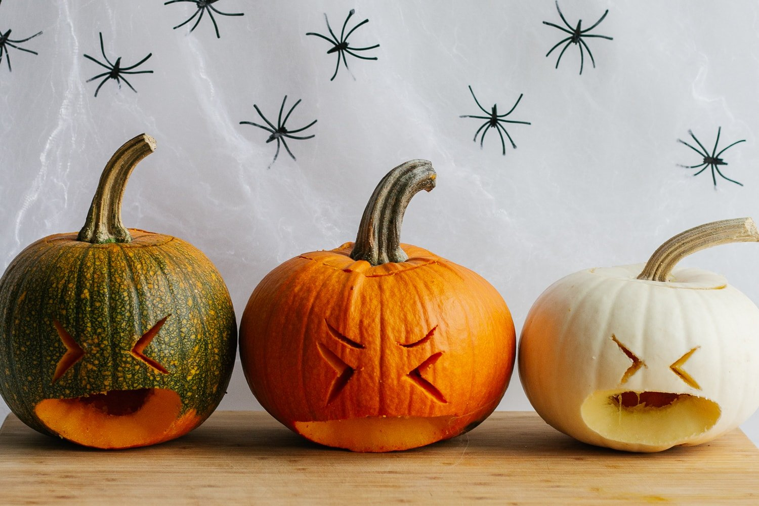 Three small carved pumpkins sitting on a wooden board.
