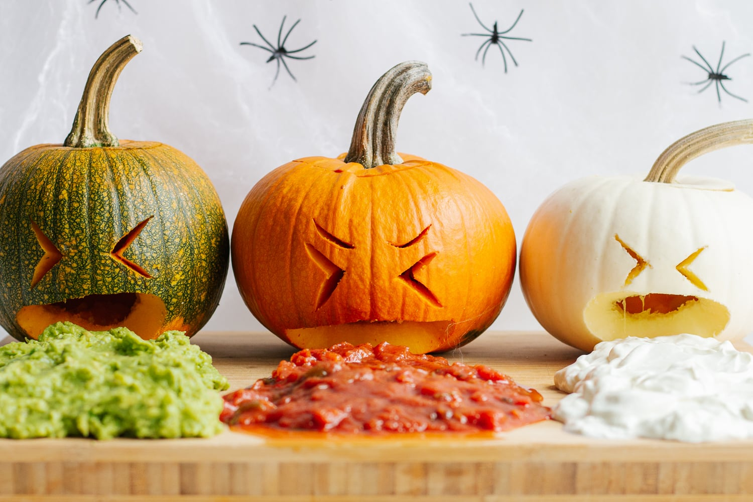 Three small carved pumpkins on a wooden board that look like they are throwing up guacamole, salsa and sour cream.
