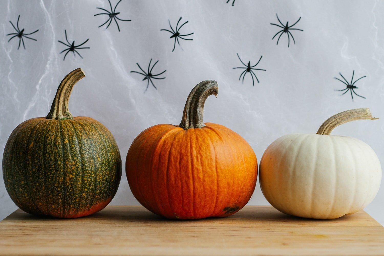 Three small pumpkins sitting on a wooden board.
