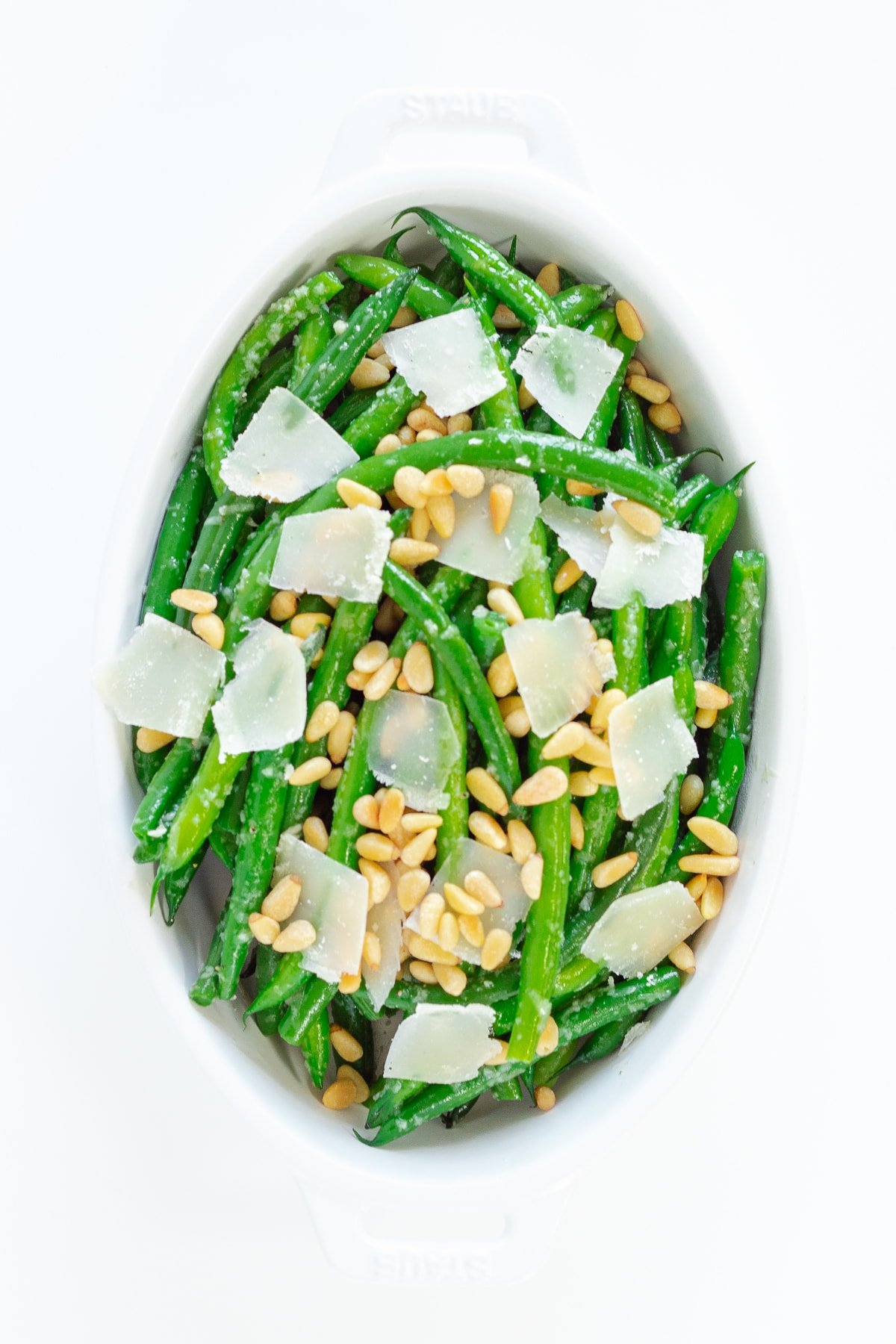 Sauteed garlic butter green beans in a white serving dish with parmesan shavings and pine nuts on top.