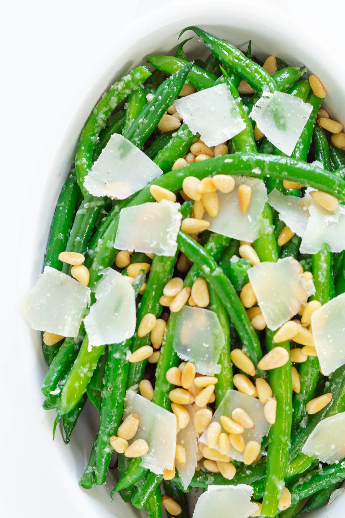 Close up photo of garlic butter green beans with parmesan and pine nuts scattered on top.