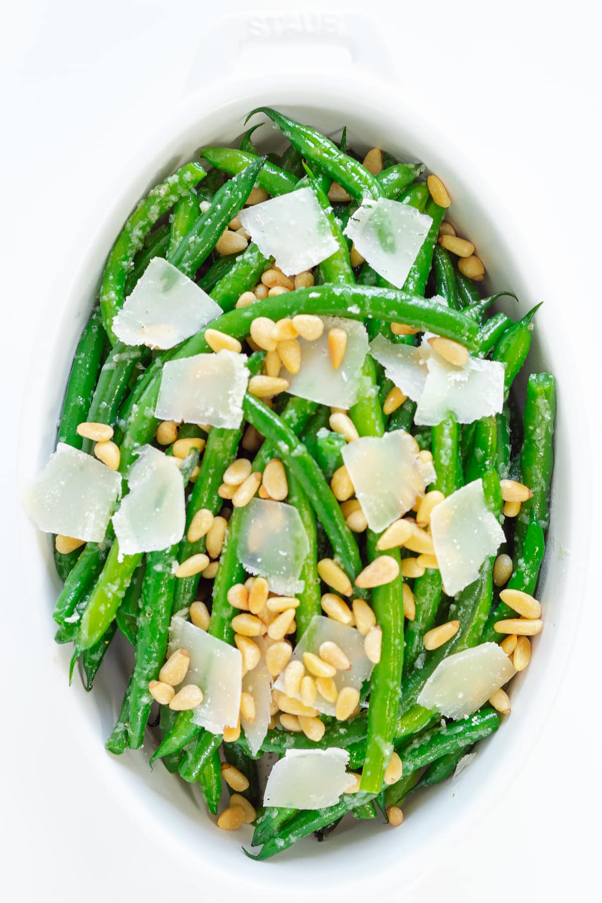 White serving dish containing garlic green beans garnished with parmesan and pine nuts.