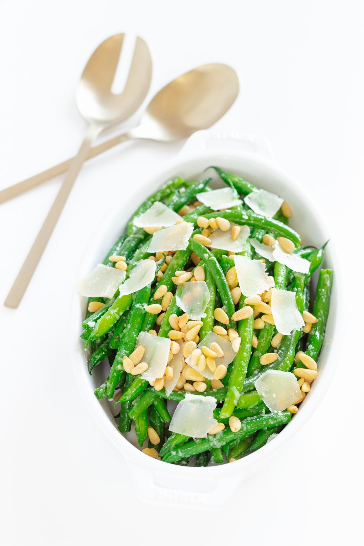 Dish of garlic butter green beans with gold serving spoons next to it.