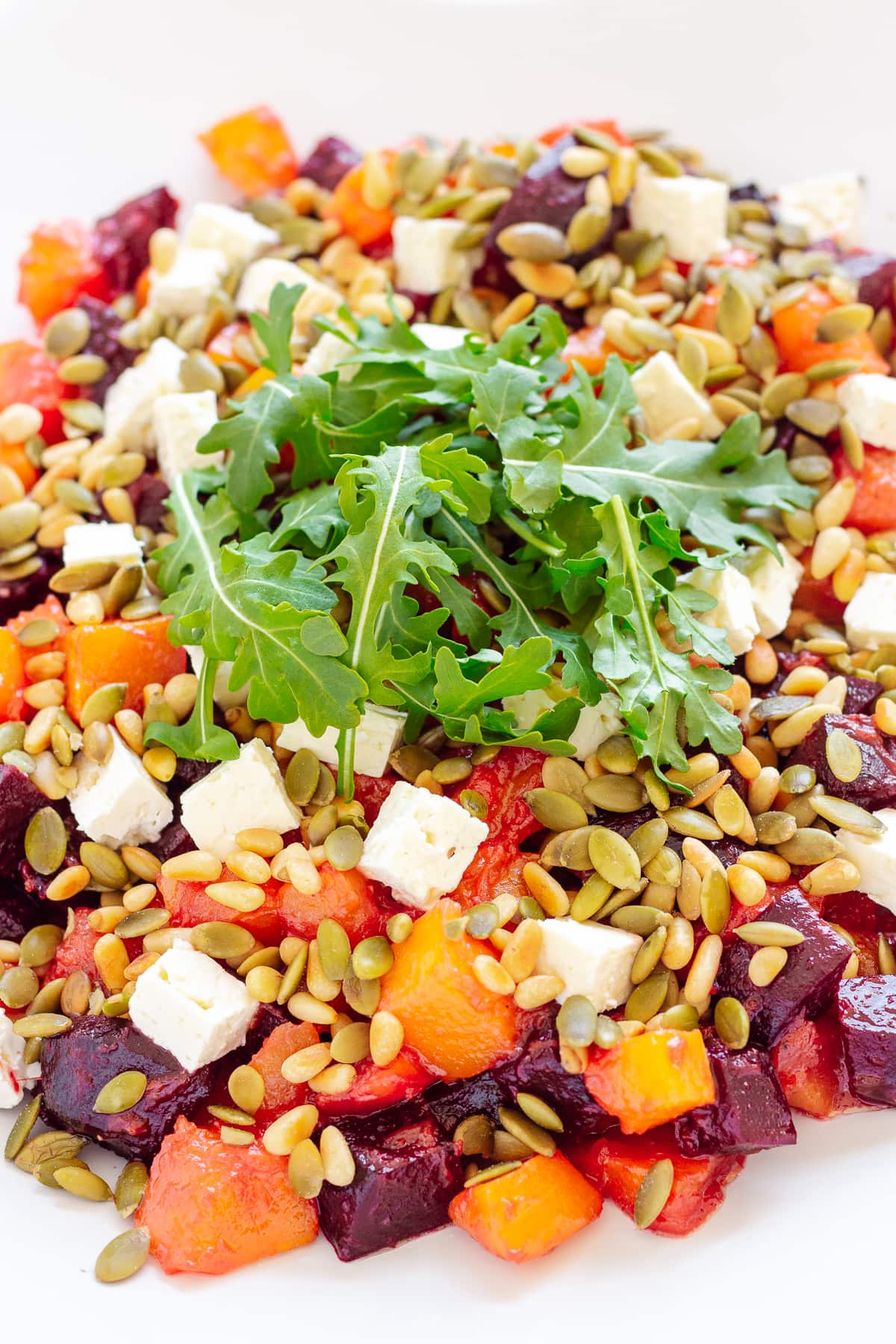 Close up photo of roasted pumpkin and beetroot salad topped with feta cheese, pine nuts, pepitas and arugula.