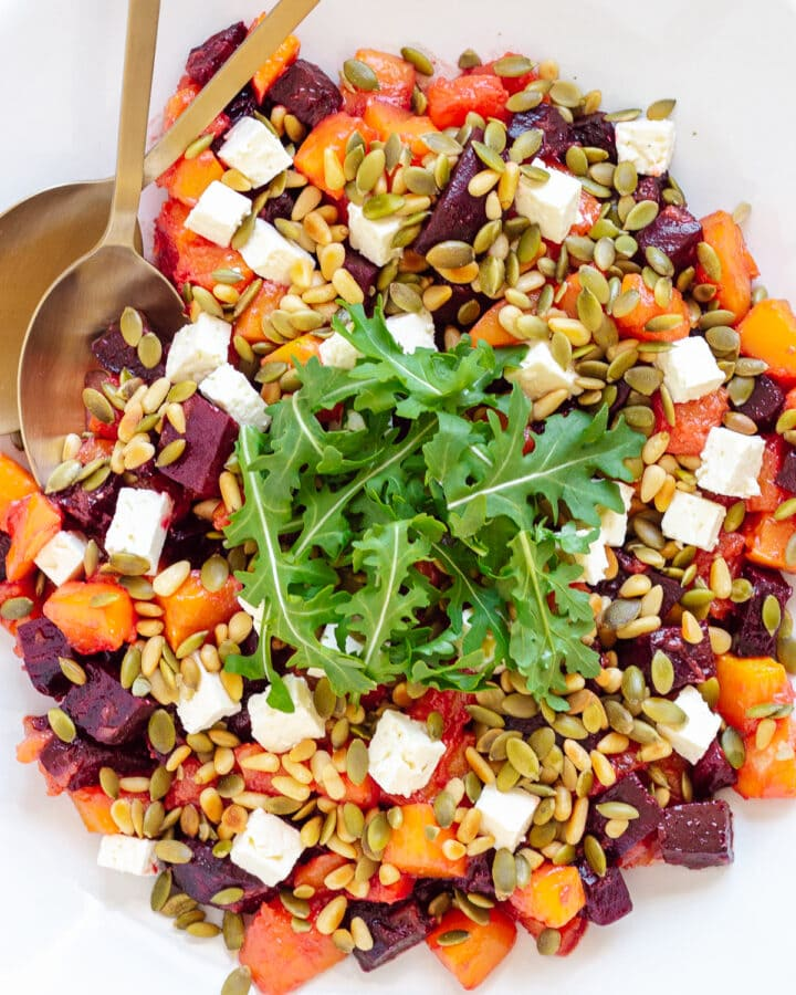 Overhead photo of roasted pumpkin and beetroot salad topped with feta, pine nuts, pepitas and arugula.