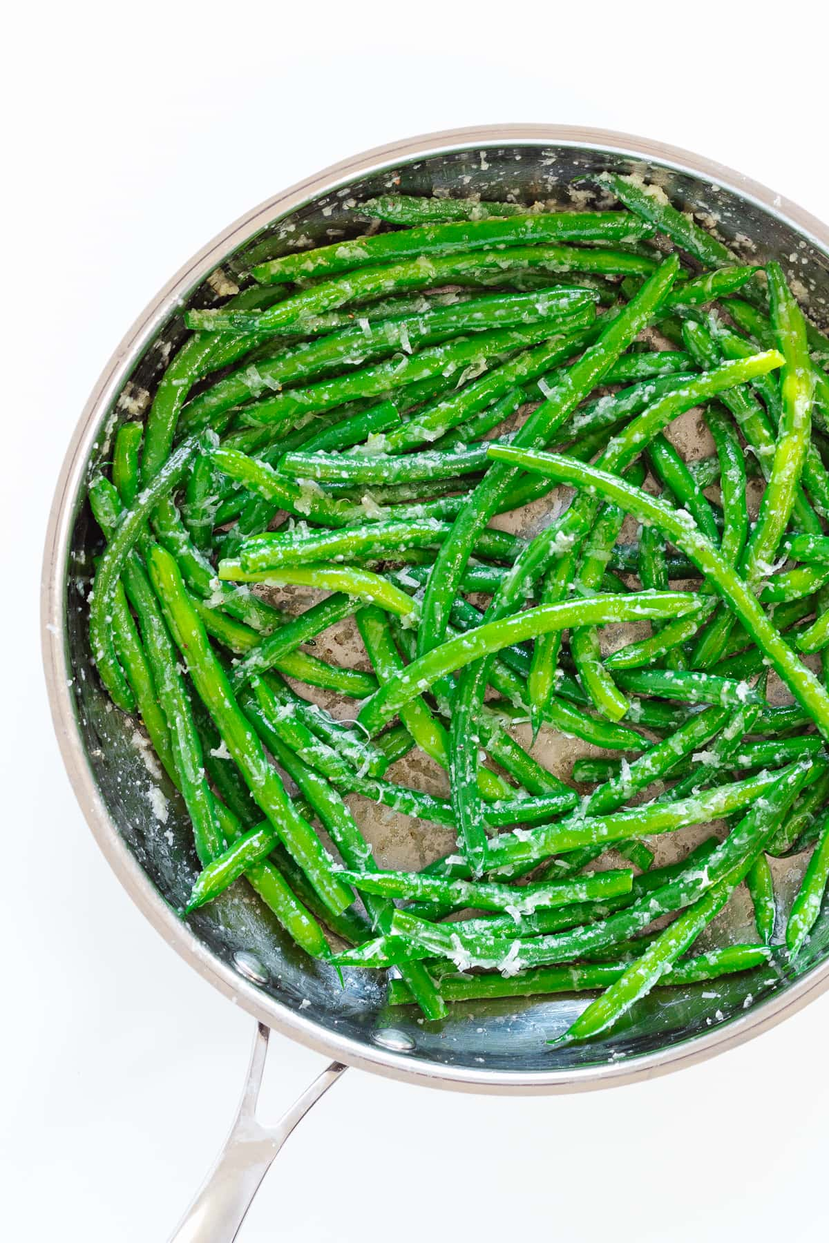 Sauteed green beans in a stainless steel frying pan.