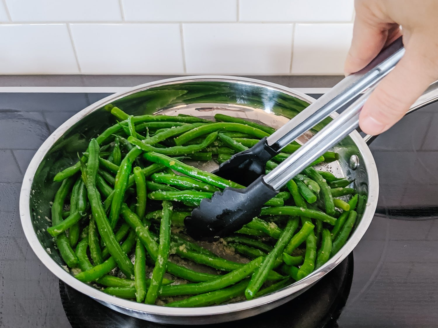 Green beans in a large pan being tossed with tongs.