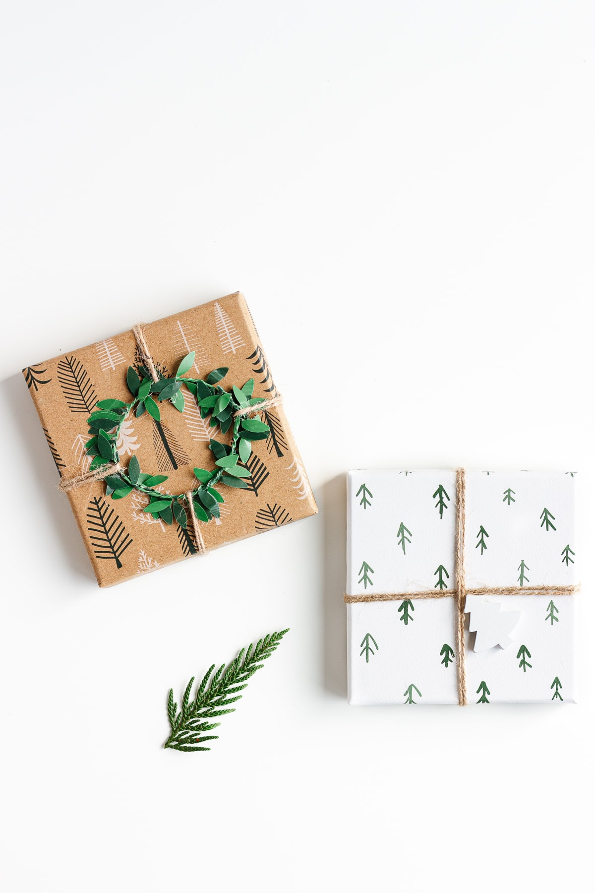 Overhead photo of two Christmas gifts and a small evergreen branch on a white background.