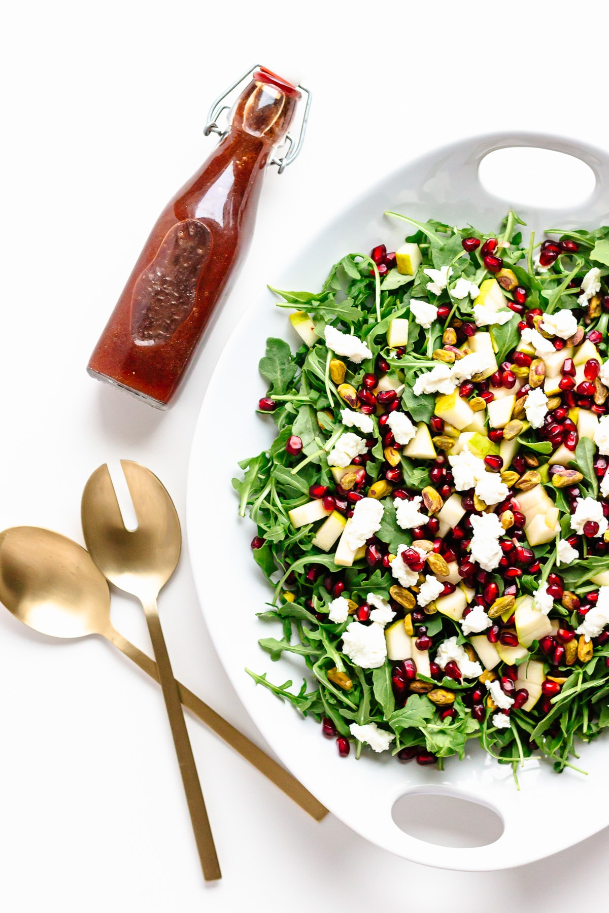 Overhead photo of a platter of winter holiday salad, gold coloured salad servers and a bottle of pomegranate vinaigrette.