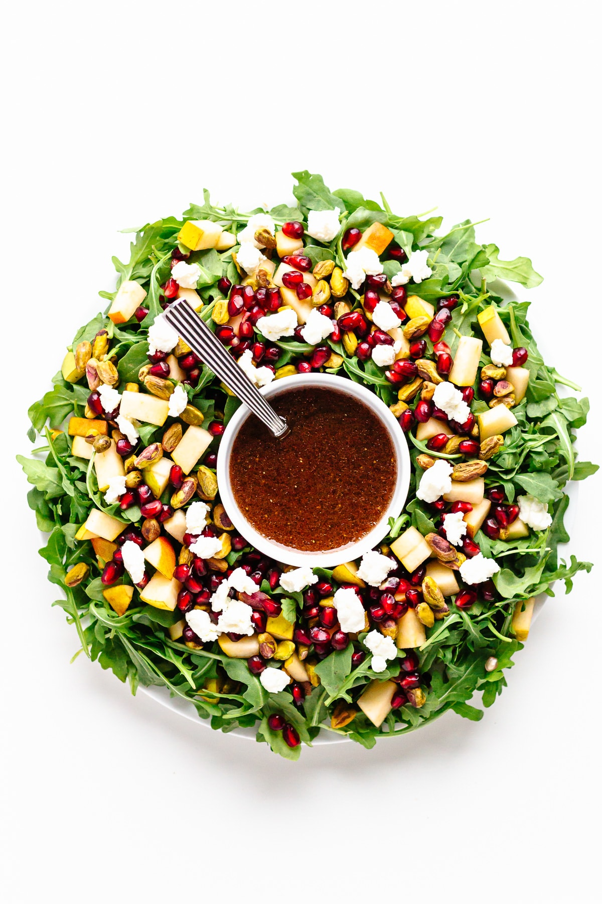 Holiday salad arranged in the shape of a Christmas wreath with a bowl of pomegranate vinaigrette in the center.