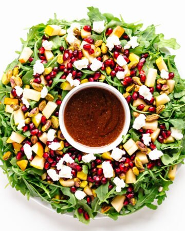 Winter Holiday Salad (arugula, pear, pomegranate arils, pistachios, goat cheese) arranged in a Christmas wreath shape with small bowl of pomegranate vinaigrette in the center.