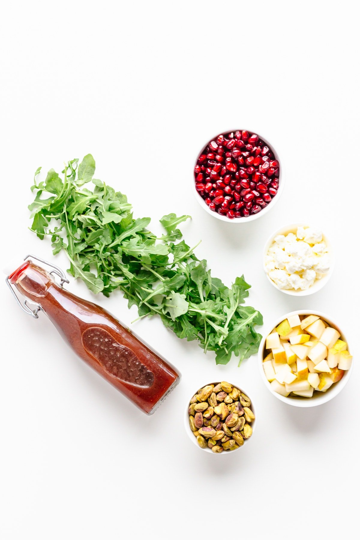Overhead photo of ingredients needed for winter holiday salad recipe: arugula, pomegranate arils, goat cheese, pear, pistachios and pomegranate vinaigrette.