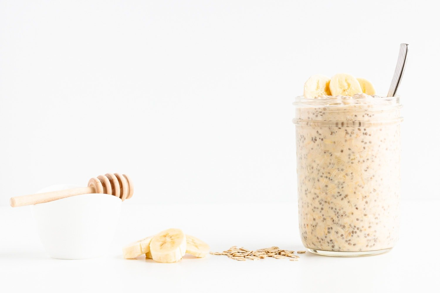 Line up of honey, banana slices, rolled oats and a jar of overnight oats against a white background.