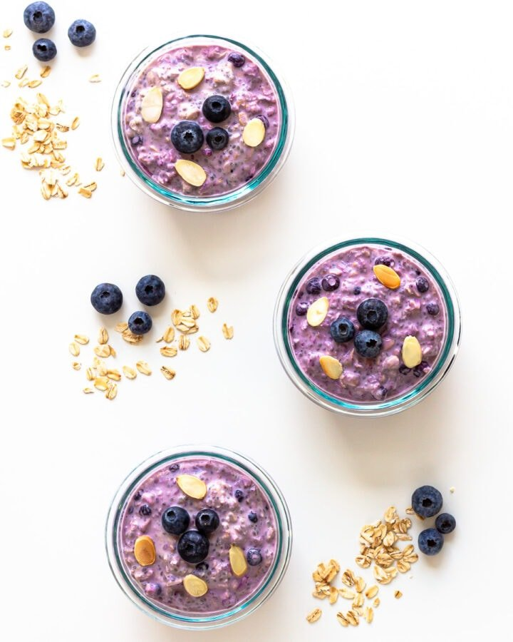Three containers of blueberry overnight oats with blueberries and rolled oats scattered beside them.