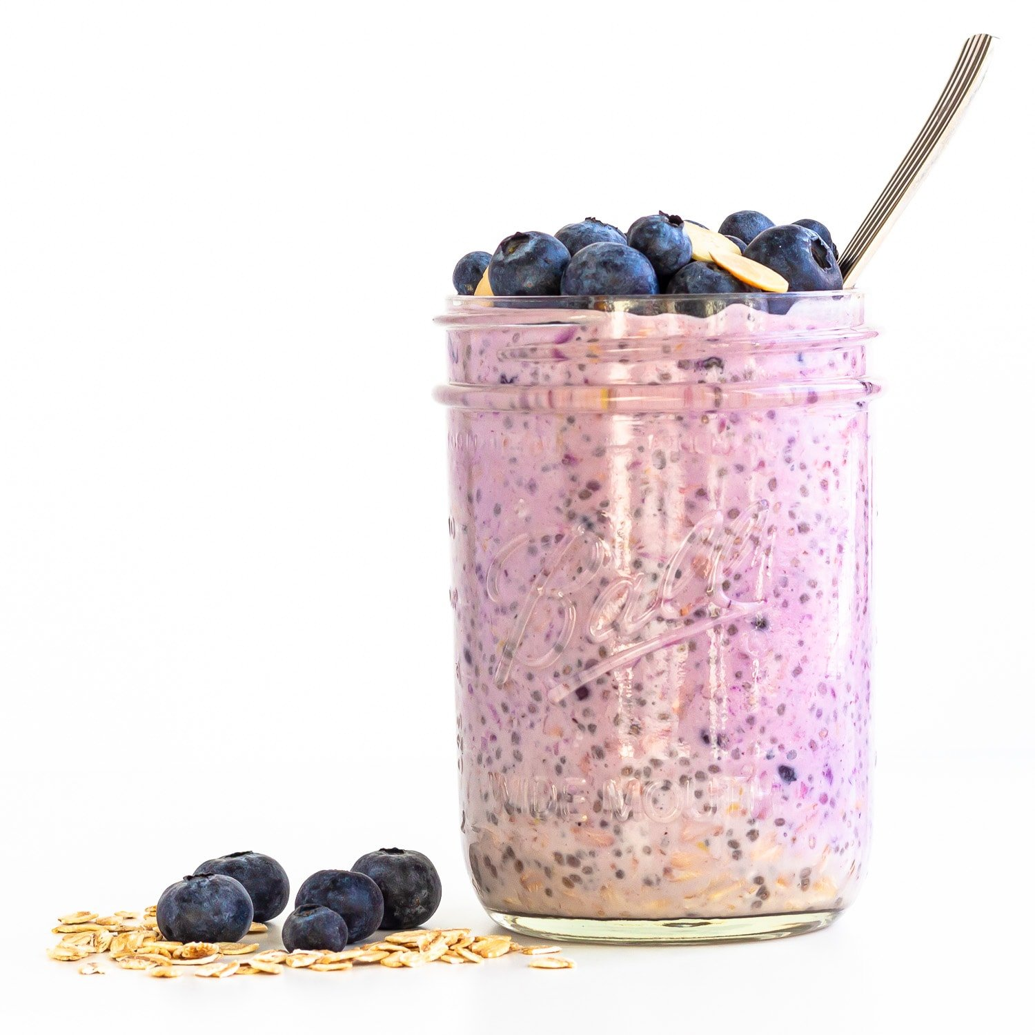 Jar of blueberry overnight oats with blueberries and rolled oats scattered next to it.