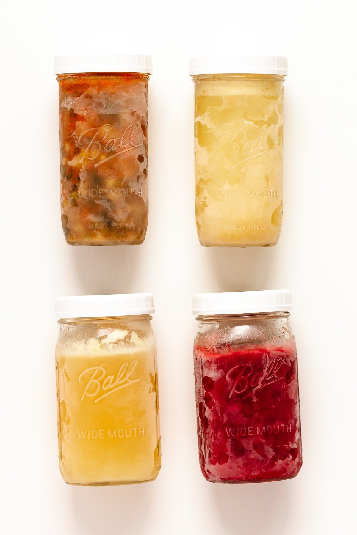 Four frozen mason jars containing different foods.
