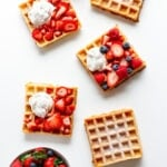 Overhead of multiple square waffles on a white background with different toppings.