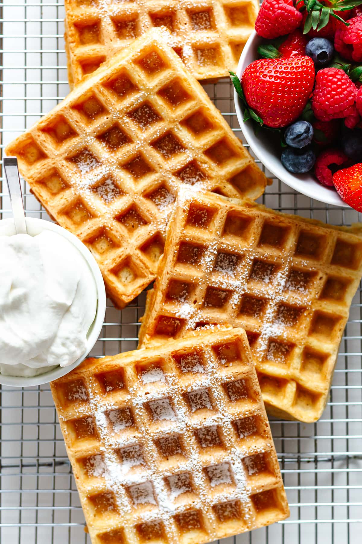 Square waffles dusted with powdered sugar on a cooling rack with bowl of berries and whipped cream.