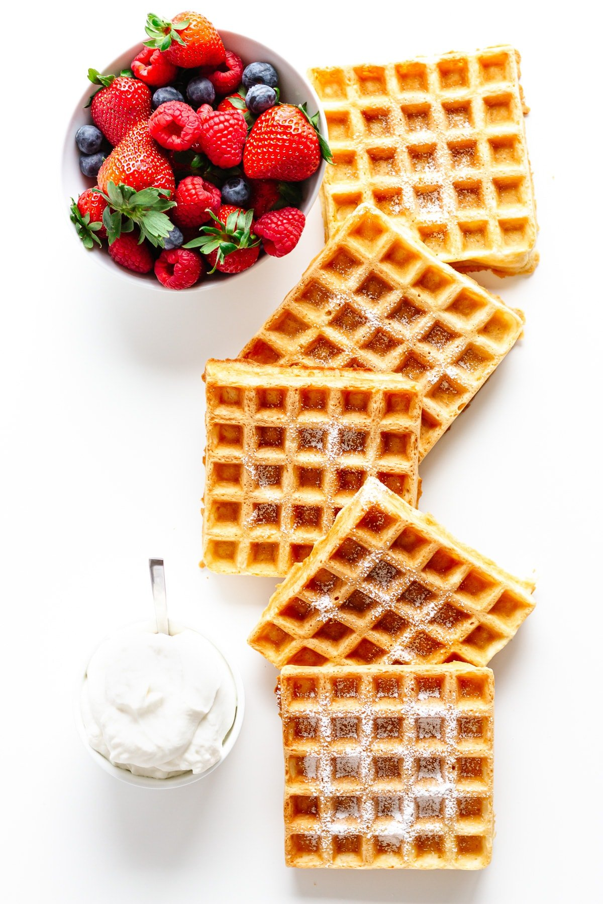 Overhead photo of square shaped waffles, bowl of berries and whipped cream on a white background.