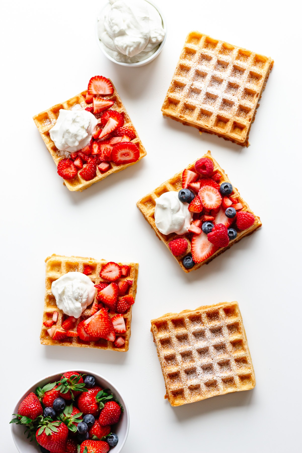 Overhead shot of five square german waffles with different toppings.