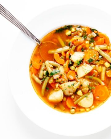 Vegetable soup in a white bowl with spoon.
