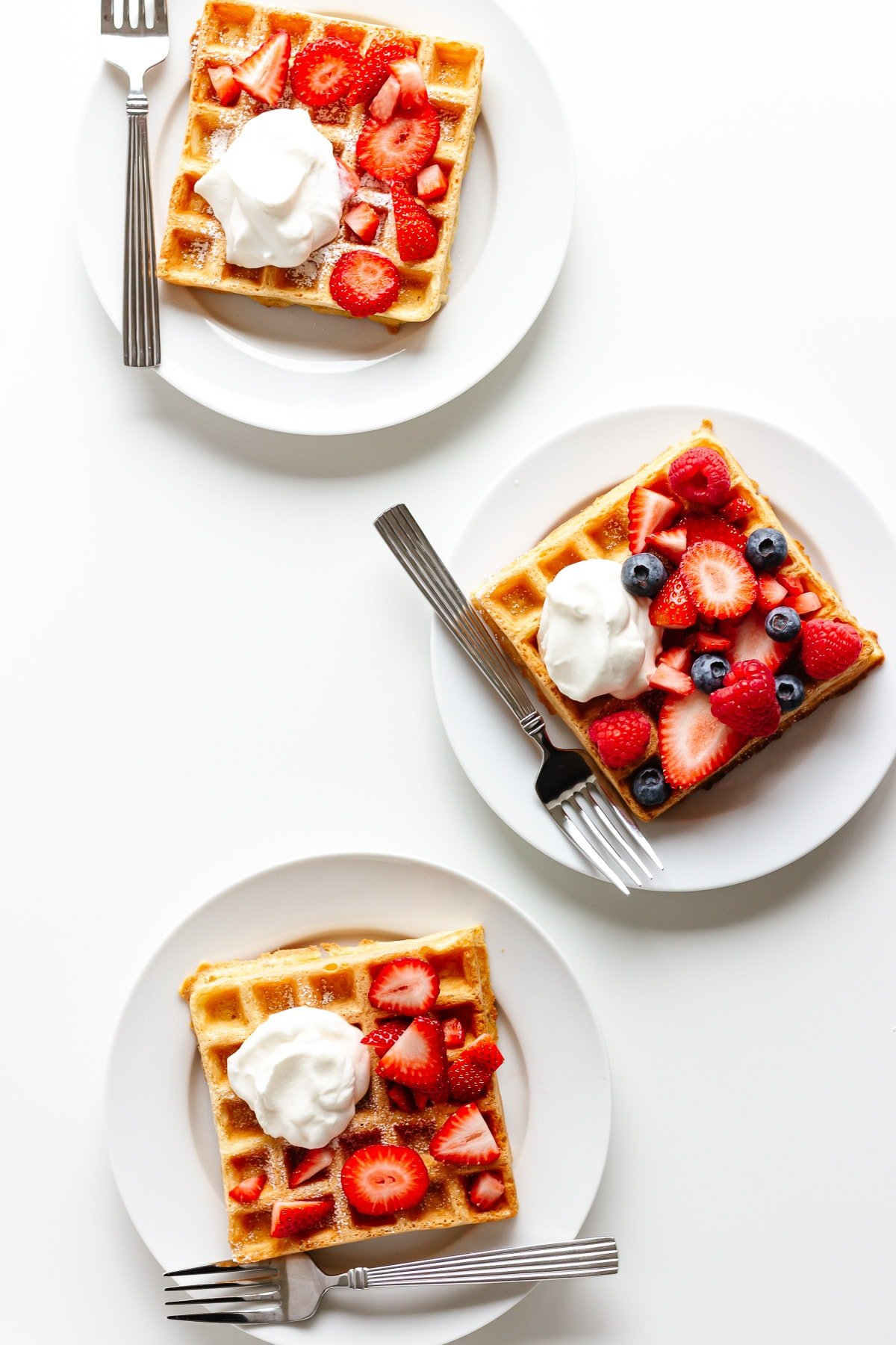 Three waffles on white plates with a fork and topped with berries and whipped cream.