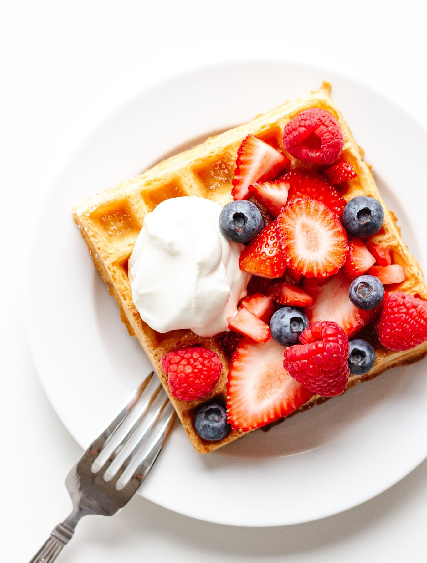 Square waffle topped with mixed berries and a dollop of whipped cream on a white plate.