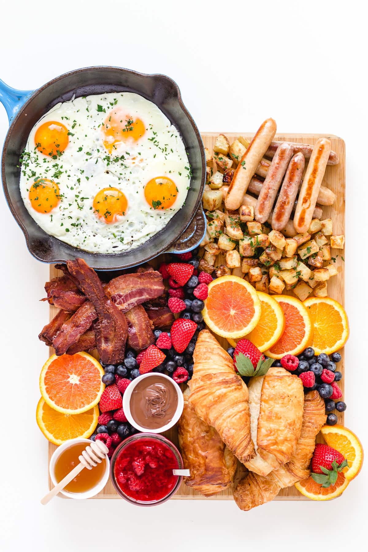 Bacon and eggs breakfast grazing board featuring fried eggs, bacon, breakfast sausages, croissants, hash browns, fresh fruit and spreads.
