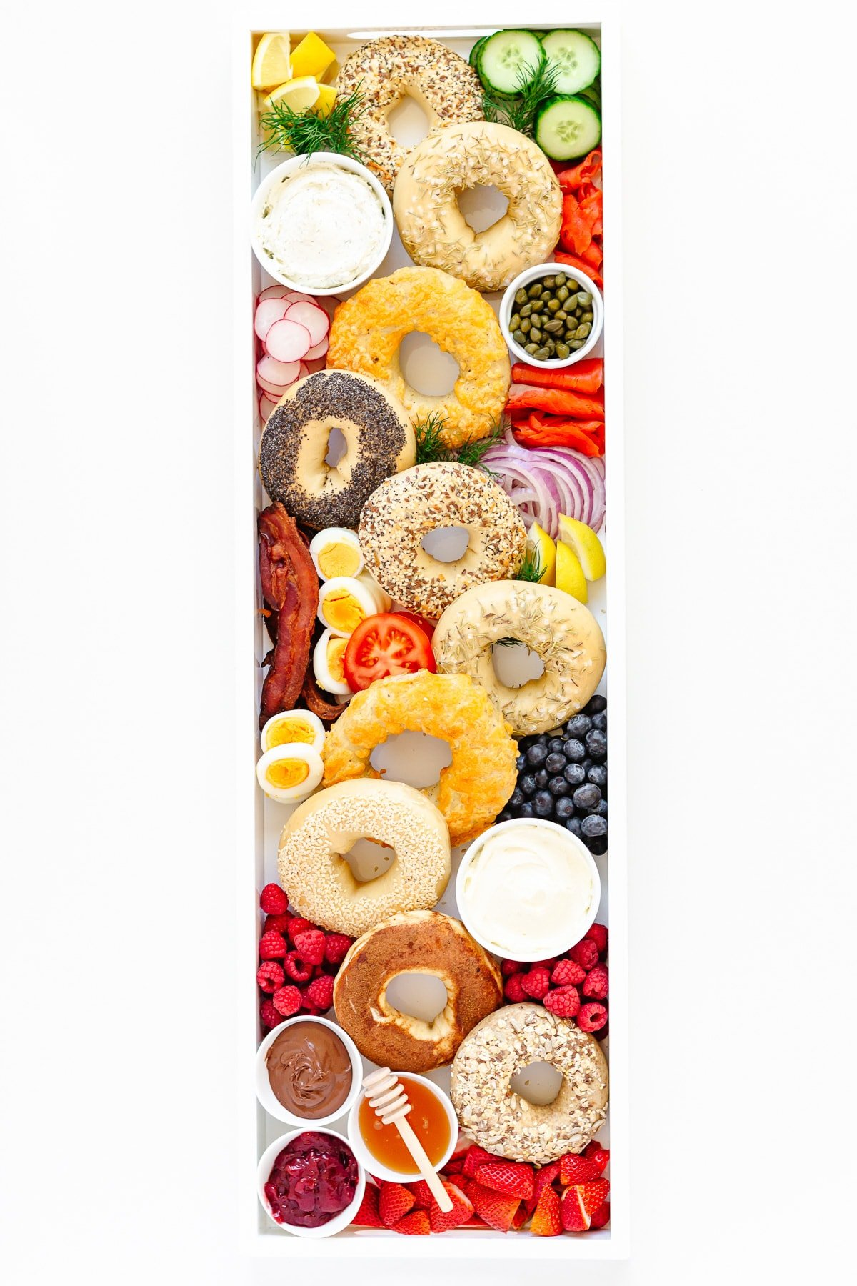Variety of different bagels and sweet and savoury toppings arranged on a long white tray.