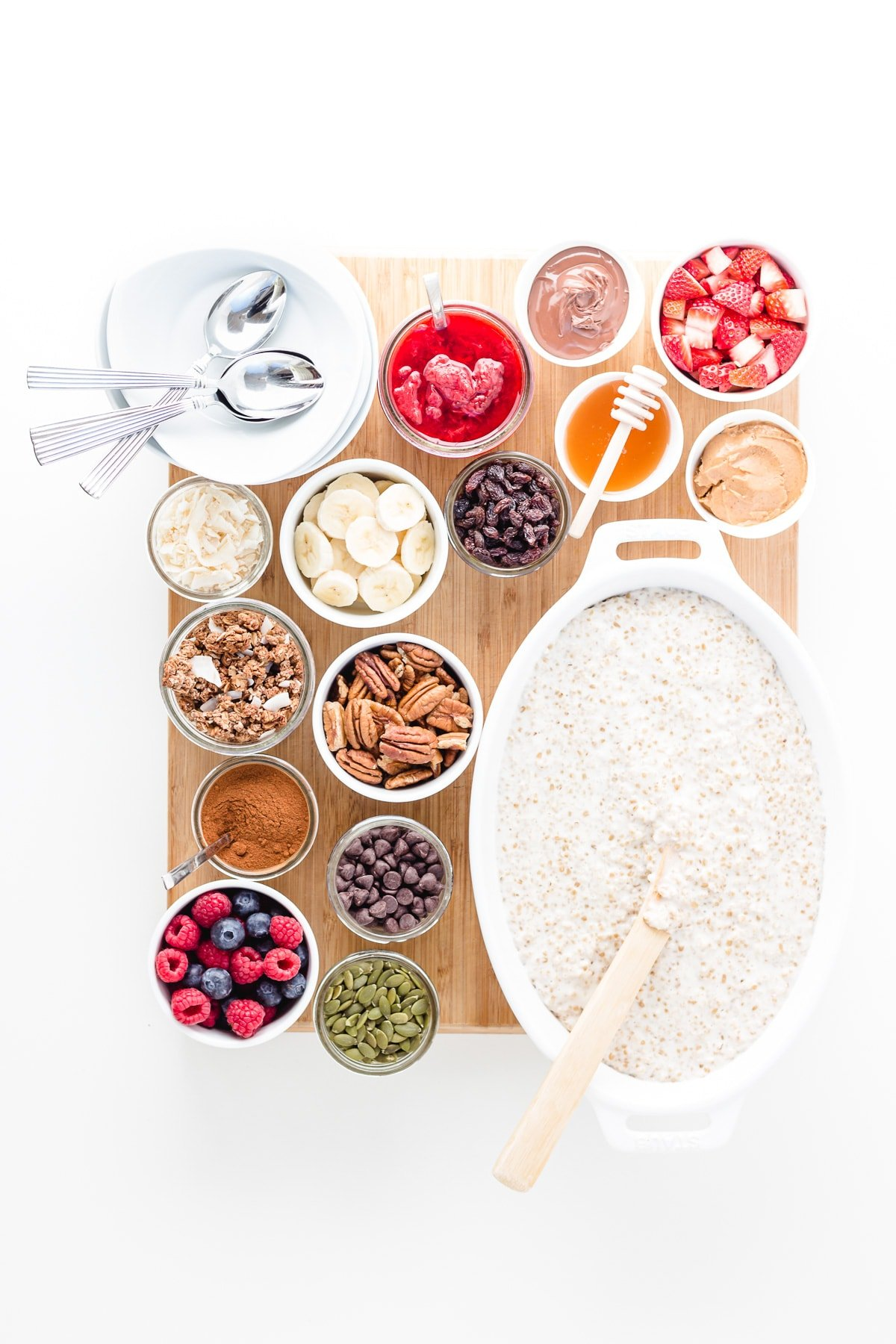 Wooden board topped with a large dish of steel cut oats, variety of small bowls of different toppings and a stack of serving bowls and spoons.