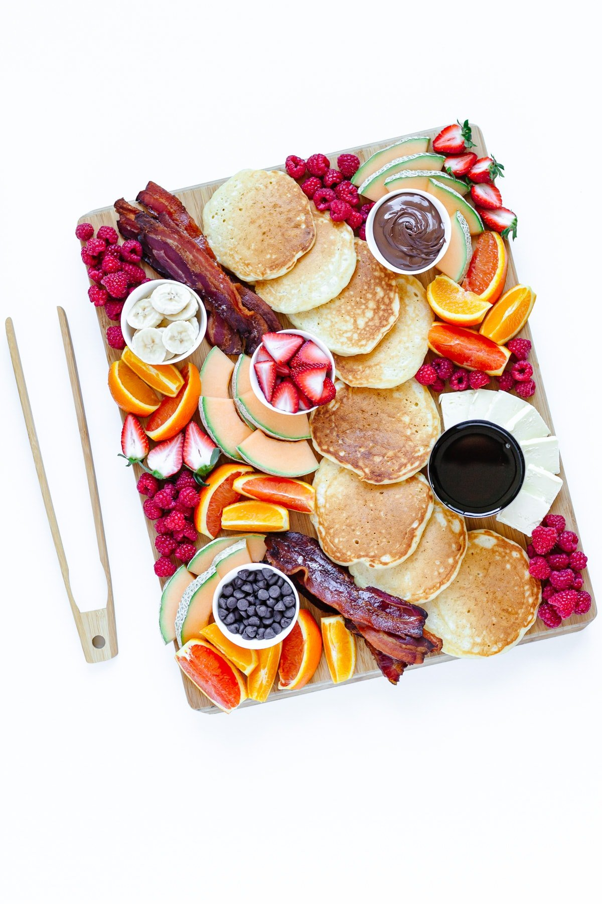 Pancake charcuterie board and wooden tongs on a white background.