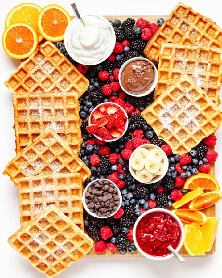 Overhead photo of a waffle breakfast board featuring waffles, bowls of toppings and fresh fruit.