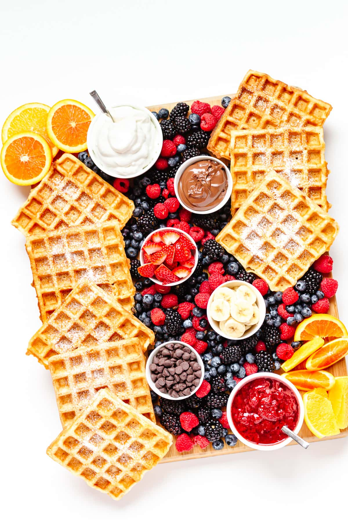A waffle brunch board  featuring german waffles, bowls of toppings and fresh fruit.