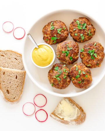 Overhead view of six German frikadellen and small bowl of mustard on a round white serving platter surrounded by some slices of rye bread and radishes.