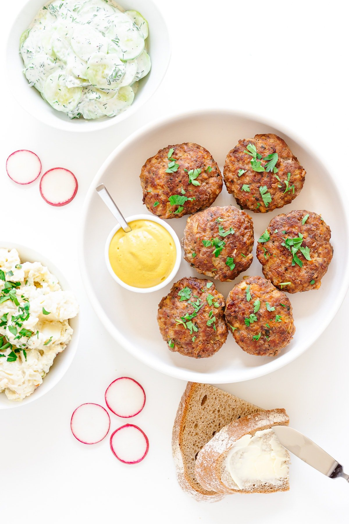 German frikadellen in a round white dish with mustard and scattering of chopped parsley.  Surrounded by cucumber salad, potato salad, German rye bread and radish slices.