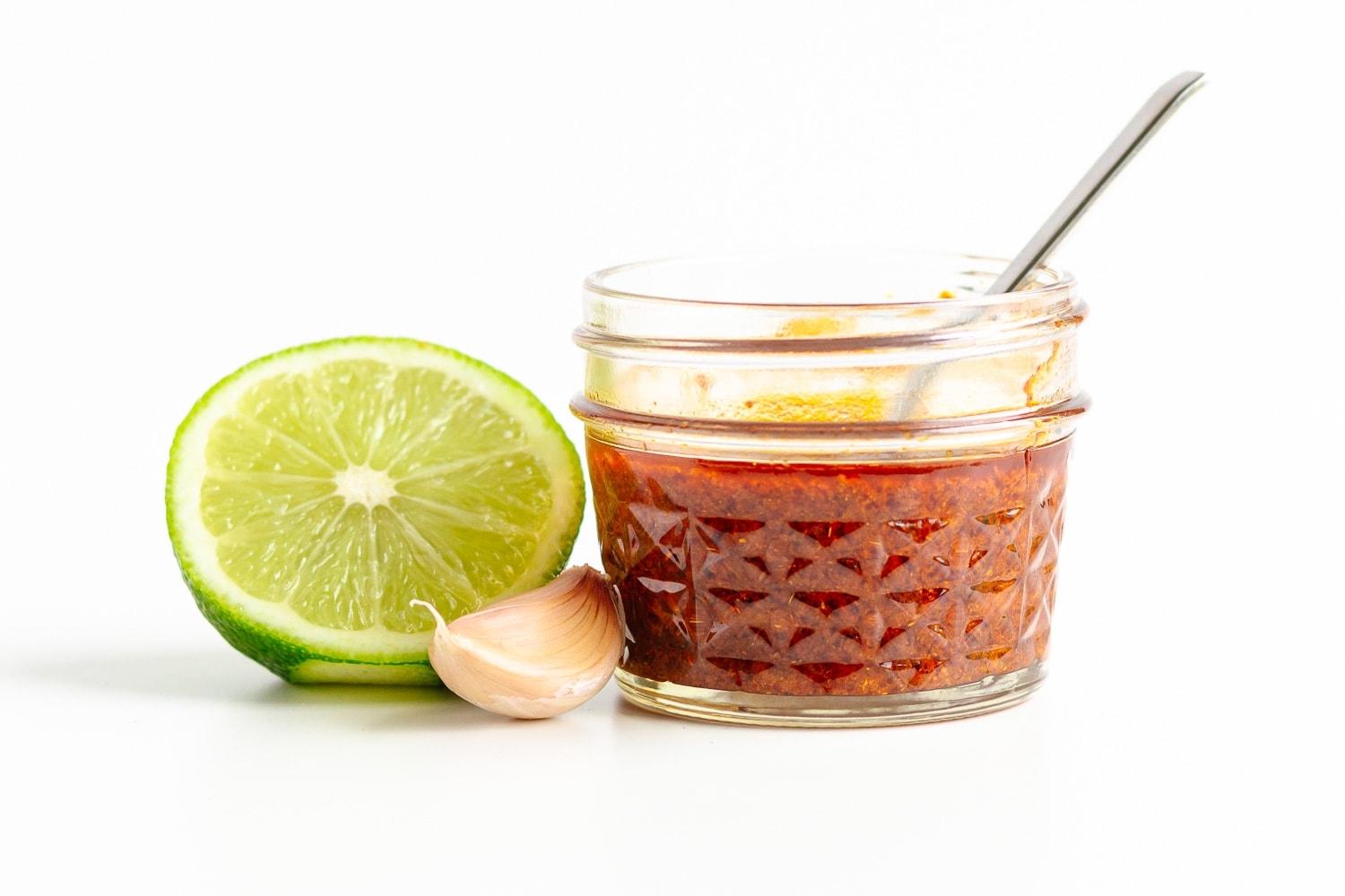 Small jar of fajita marinade with half a lime and a garlic clove next to it.