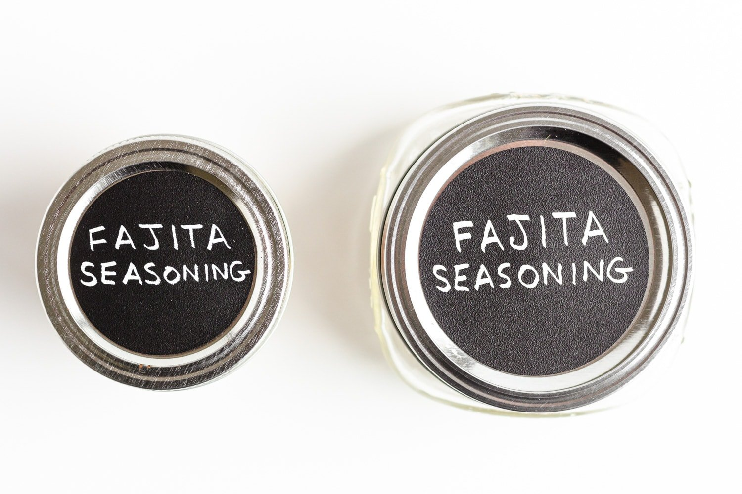 """The top of of two small mason jars that have chalk labels on top with the words """"Fajita Seasoning""""."""