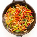 Fajita veggies sizzling in a cast iron skillet.