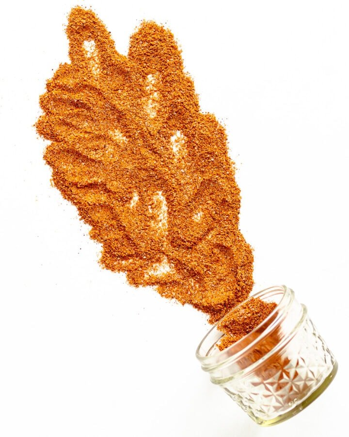 Small glass jar on its side with fajita seasoning spilling out across a white background.