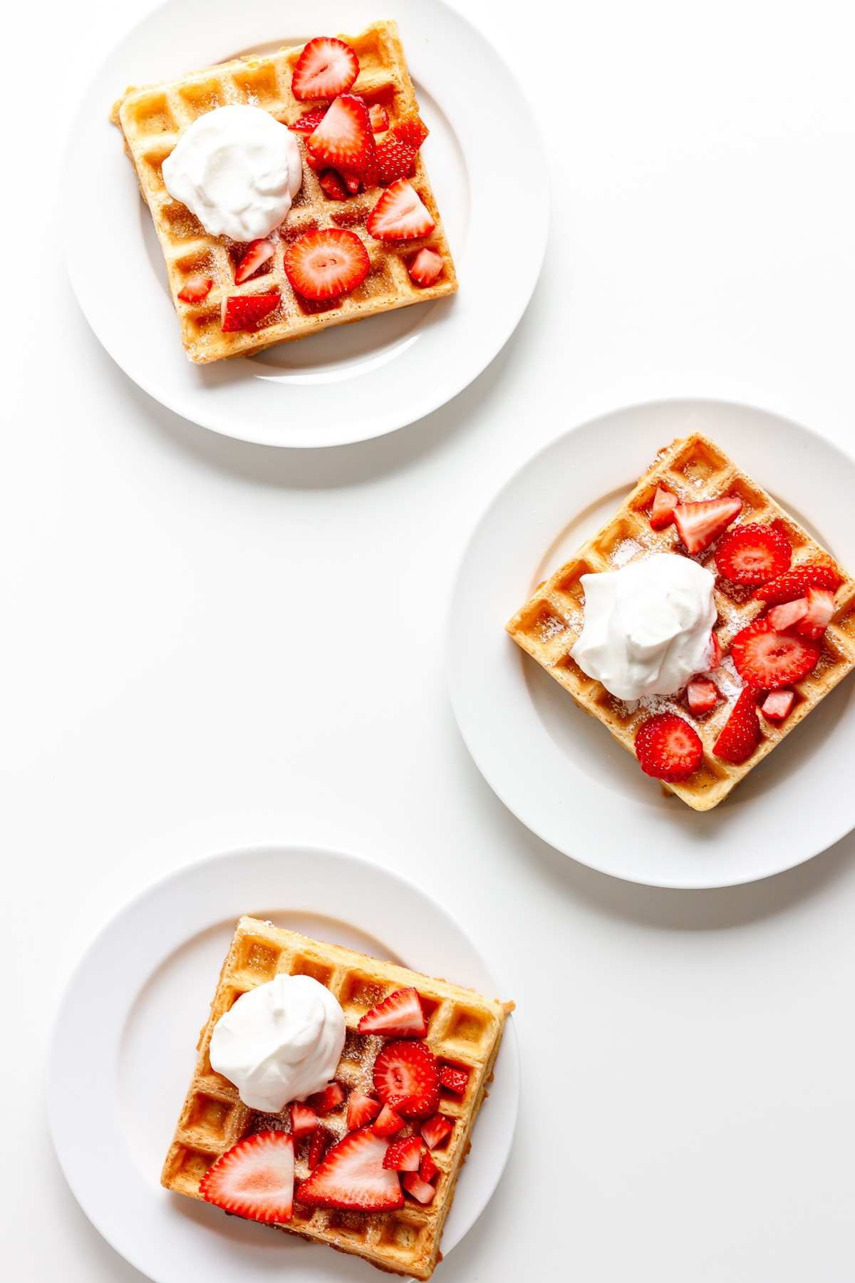 Three white plates each holding one square waffle topped with fresh strawberries and whipped cream.