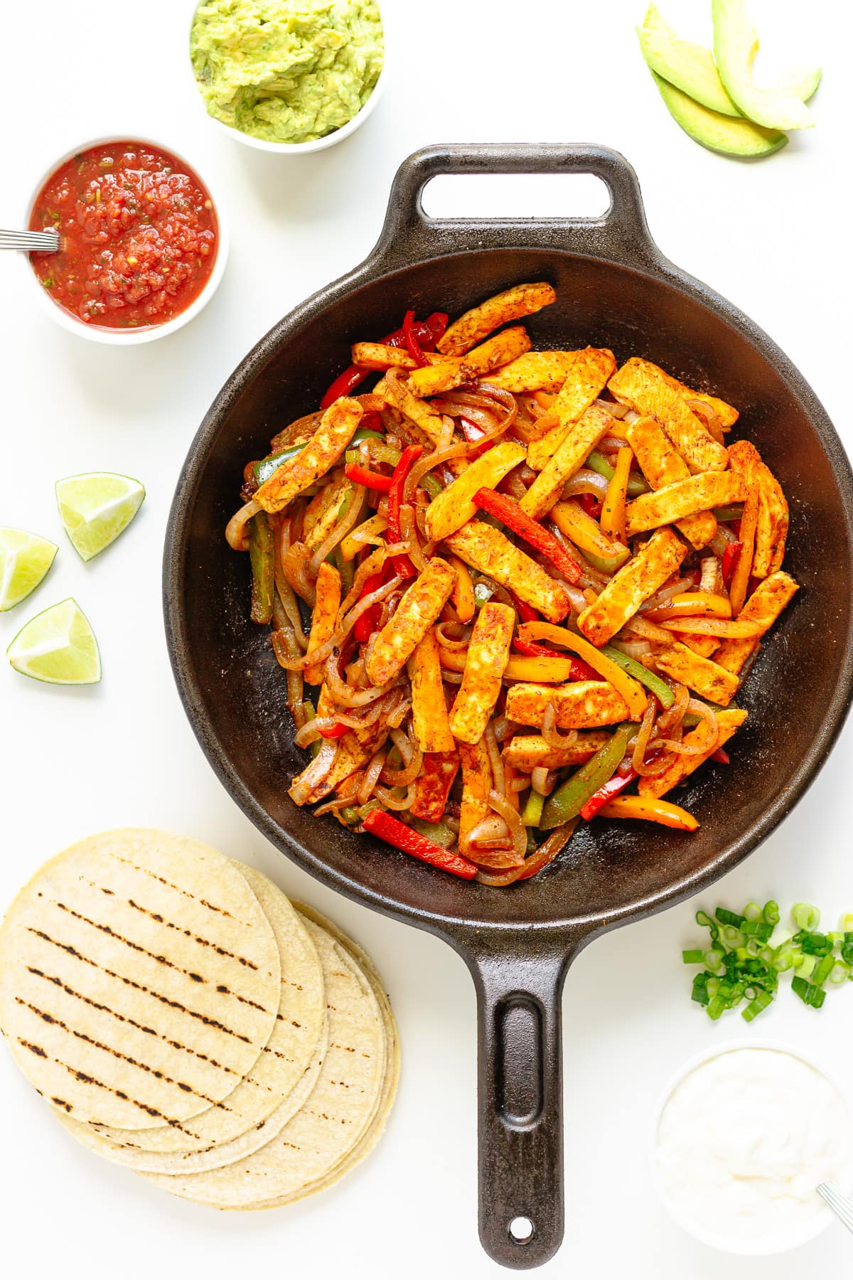 Halloumi veggie fajita mixture in a cast iron skillet with tortillas and a variety of toppings around it.