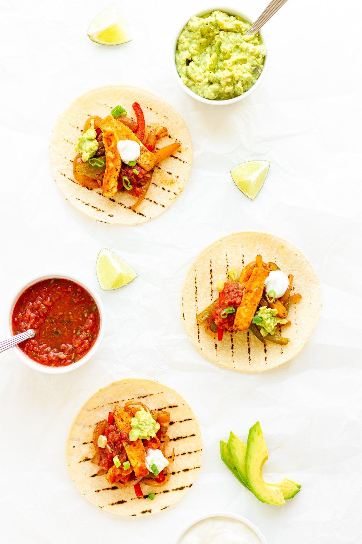 Three halloumi fajitas on a white background with various toppings laid out around them.