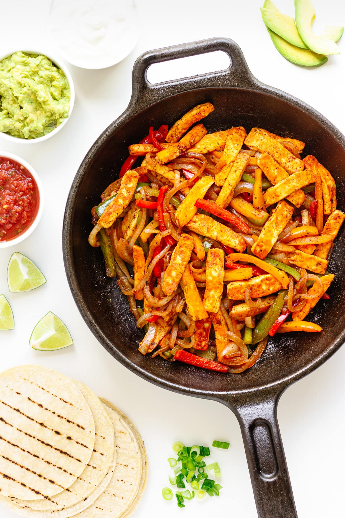 Flat lay of halloumi vegetable fajita mixture in a cast iron skillet surrounded by tortillas and toppings.