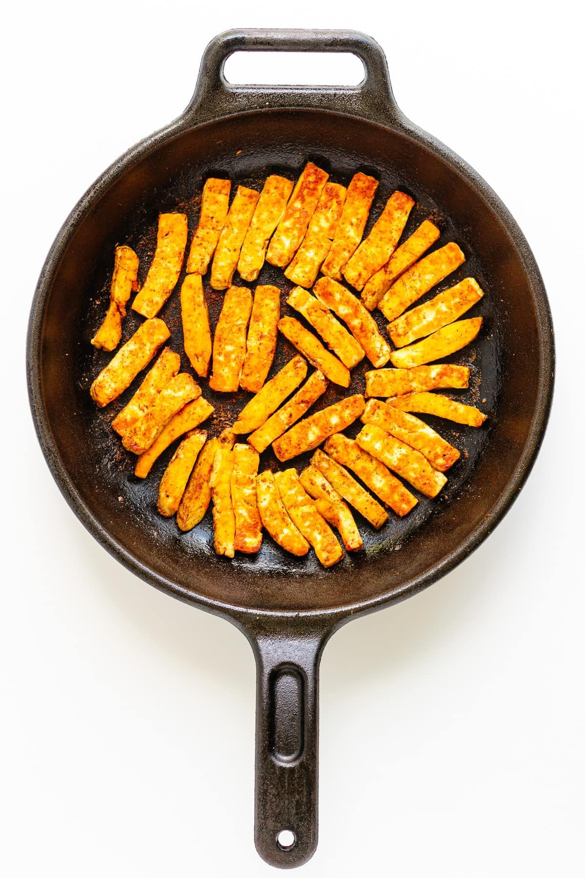 Fried halloumi strips in a cast iron skillet.