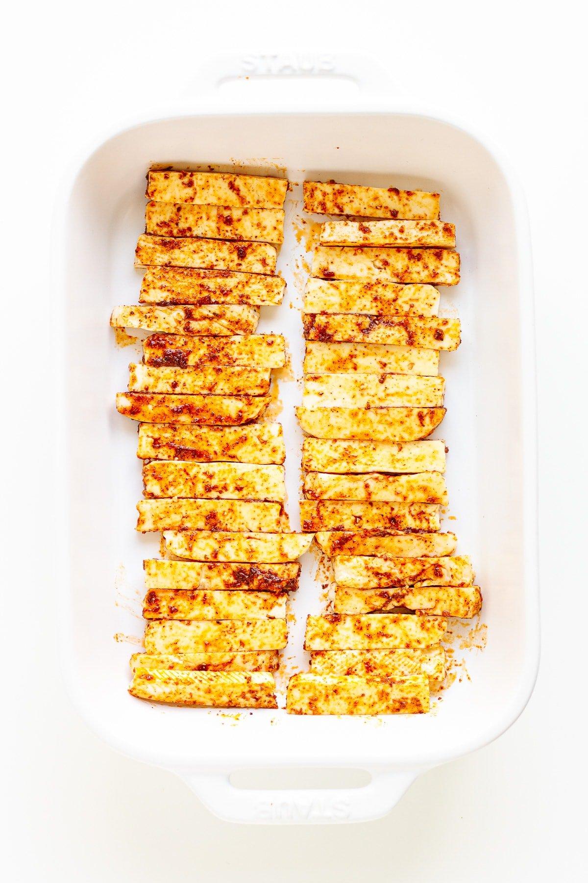 Seasoned halloumi strips in a white casserole dish.
