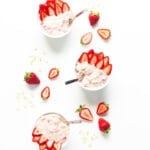 Overhead view of three bowls of strawberry overnight oats garnished with strawberry slices.