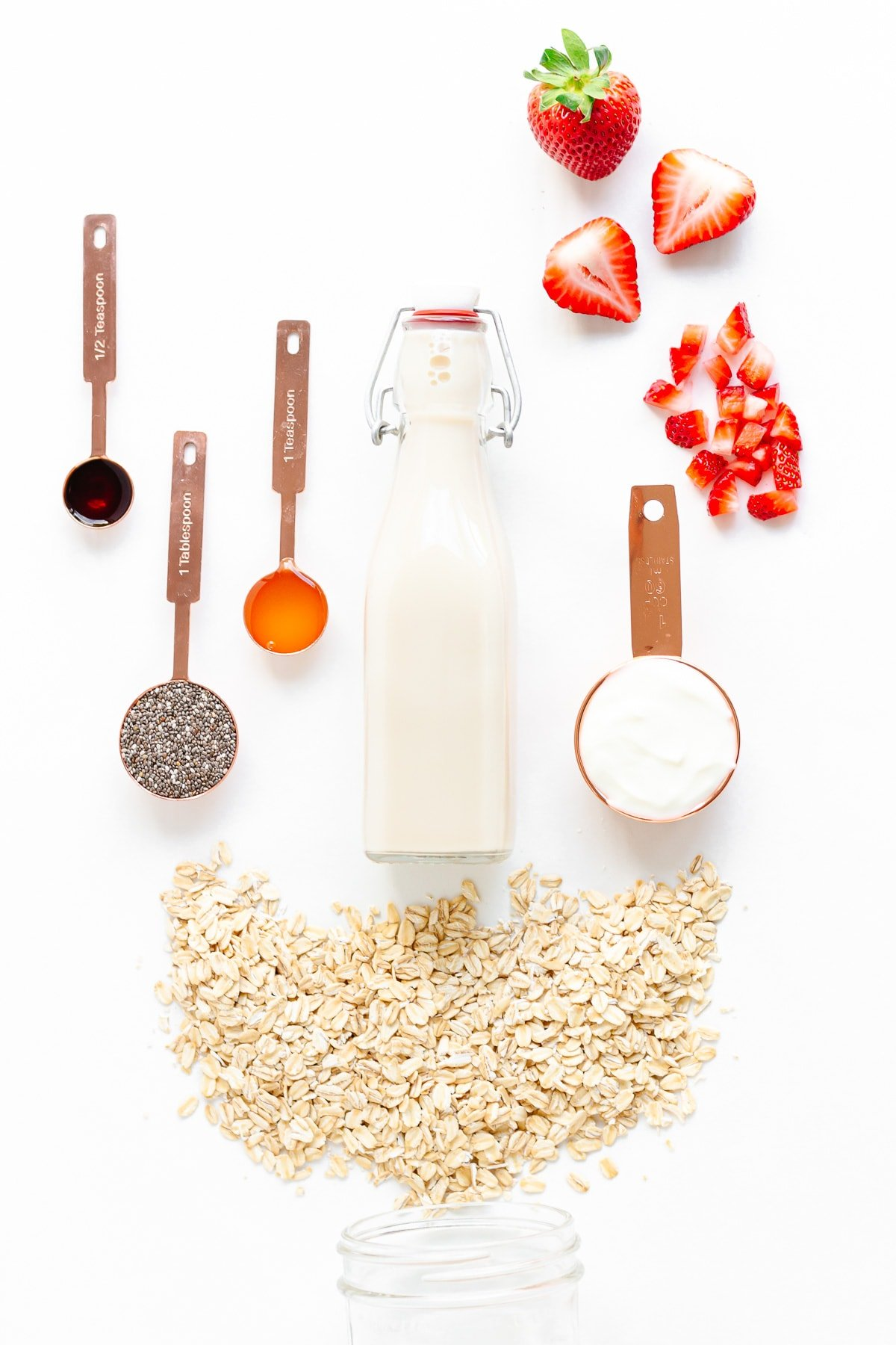 Ingredients needed to make strawberry overnight oats arranged on a white background.